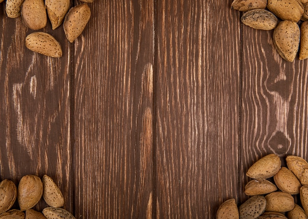 Vue de dessus des amandes en coquille éparpillées sur fond de bois avec copie espace