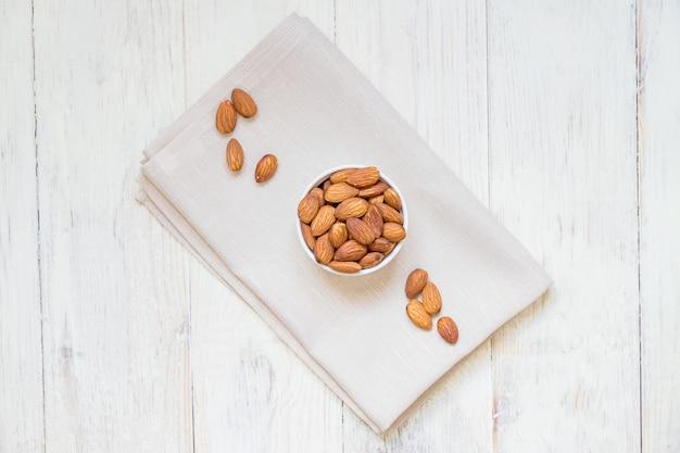 Vue de dessus d'amandes grillées dans un bol en porcelaine blanche sur une serviette en tissu et une table en bois blanche
