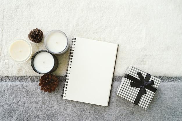 Vue de dessus de l'ambiance chaleureuse et chaleureuse avec planificateur de cahier vierge sur fond tricoté et bougie avec boîte-cadeau