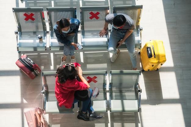 Vue de dessus d'amis asiatiques avec masque au siège avec panneau de distanciation sociale près des bagages pour attendre le départ dans le terminal de l'aéroport. nouveau mode de vie normal de voyage ou de vacancier pour empêcher le delta de covid-19
