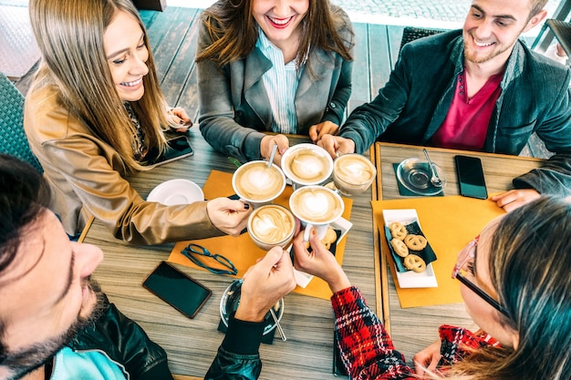 Vue de dessus d'amis heureux grillant un cappuccino au café-restaurant