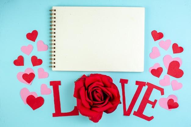 Vue de dessus amour majuscule autocollants coeur rouge et rose cahier sur table bleue