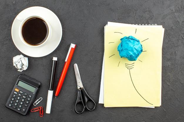 Vue de dessus ampoule idealight sur bloc-notes ciseaux calculatrice tasse de thé stylo rouge et marqueur noir sur fond noir