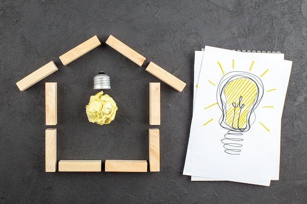 Vue de dessus de l'ampoule idealight dans des blocs de bois en forme de maison ampoule idealight dessin sur le bloc-notes sur fond noir