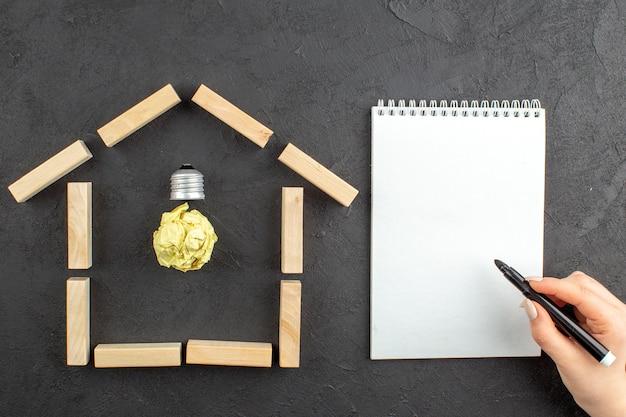Vue de dessus de l'ampoule idealight dans des blocs de bois en forme de maison, un marqueur noir de bloc-notes dans une main féminine sur fond noir