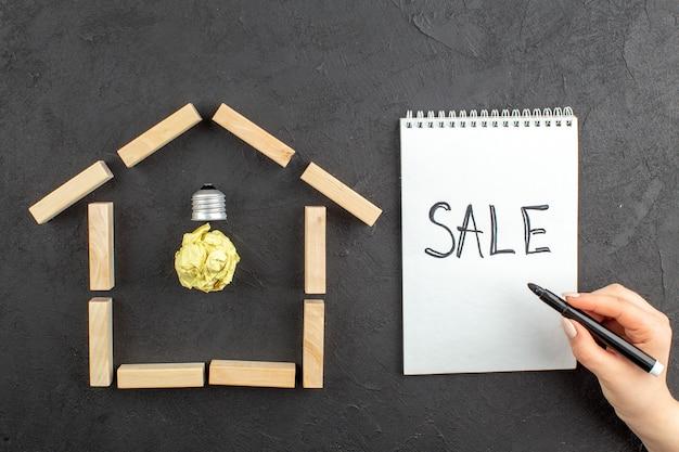 Vue de dessus de l'ampoule idealight dans la vente de blocs de bois en forme de maison écrite sur le marqueur noir du bloc-notes dans la main féminine sur le noir