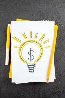 Vue de dessus de l'ampoule idealight jaune écrite sur un marqueur jaune du bloc-notes et un crayon sur le noir