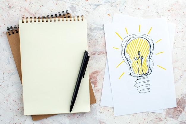 Vue de dessus de l'ampoule idée dessin sur papier stylo sur bloc-notes sur table