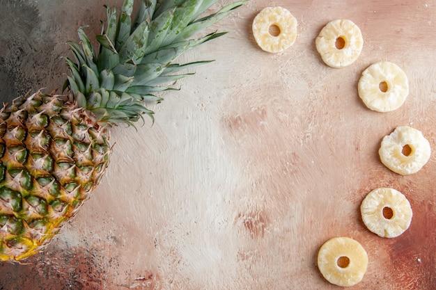 Vue de dessus ananas frais anneaux d'ananas secs sur fond beige avec lieu de copie