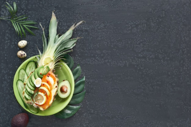 Vue de dessus sur ananas avec saumon fumé et tranches d'avocat au citron et œuf de caille
