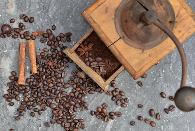 Vue de dessus sur l'ancien moulin à café plein de café et de grains avec des épices sur fond de marbre gris