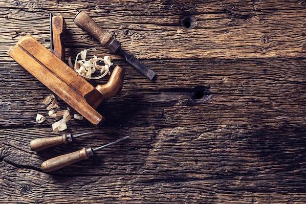 Vue de dessus ancienne raboteuse et autres outils de menuisier vintage dans un atelier de menuiserie.