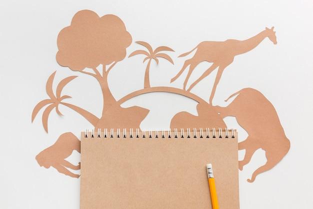 Vue de dessus des animaux en papier avec globe et cahier pour la journée des animaux