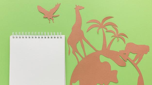 Vue de dessus des animaux en papier avec planète et cahier pour la journée des animaux