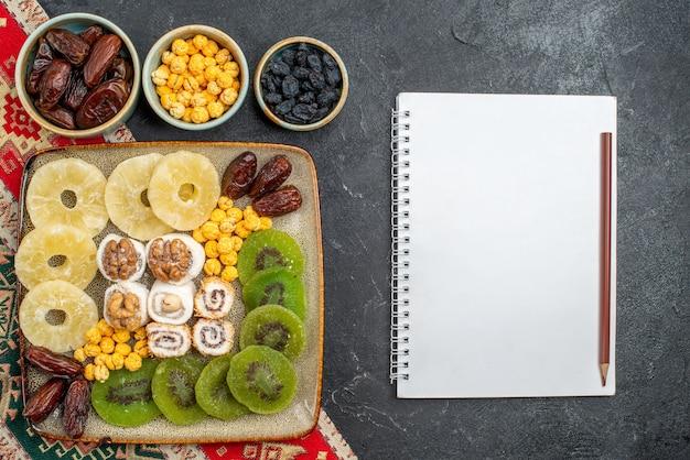 Vue de dessus anneaux d'ananas de fruits secs en tranches et kiwis sur fond gris fruits secs raisins secs vitamine aigre santé