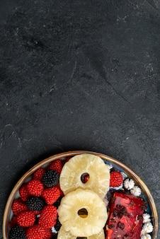 Vue de dessus des anneaux d'ananas séchés avec des baies de confiture sur un bureau gris