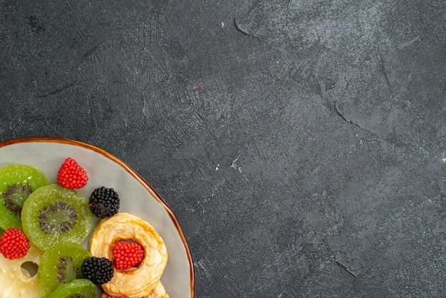 Vue de dessus des anneaux d'ananas séchés avec des kiwis et des pommes séchés sur la surface gris foncé