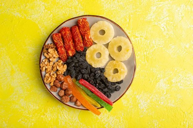 Vue de dessus des anneaux d'ananas séchés avec des noix de nougat aux fruits secs sur la surface jaune