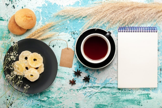 Vue de dessus anneaux d'ananas séchés avec tasse de thé sur le fond bleu clair gâteau cuire au four biscuit aux fruits biscuit au sucre sucré