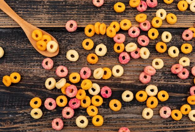 Vue de dessus des anneaux de maïs avec petite cuillère sur une surface en bois sombre horizontal