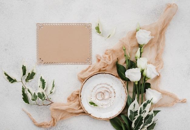 Vue de dessus des anneaux de mariage avec des fleurs sur la table