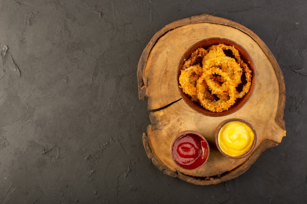Une vue de dessus des anneaux de poulet frit à l'intérieur de la plaque avec du ketchup et de la moutarde