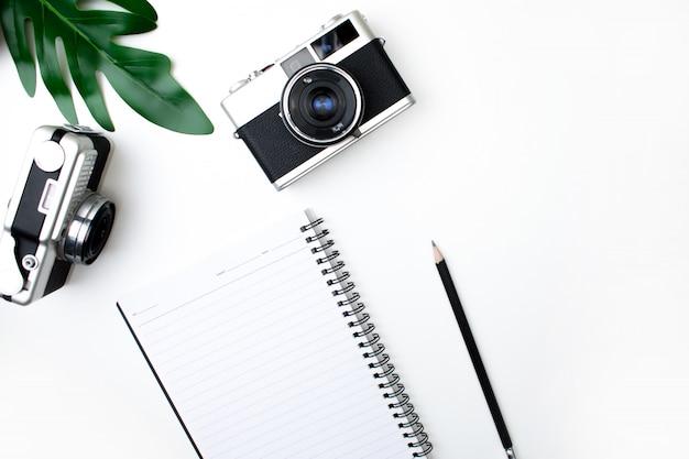 Vue de dessus de l'appareil photo argentique avec carnet, crayon et feuilles. fond blanc isolé