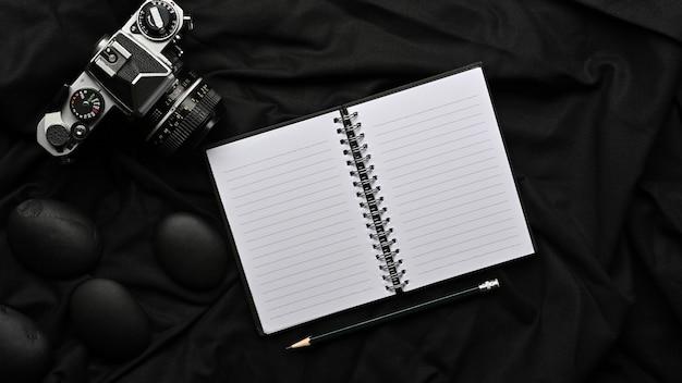 Vue de dessus de l'appareil photo crayon cahier vierge ouvert et décoration sur table noire