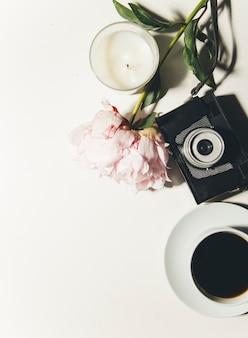 Vue de dessus de l'appareil photo vintage tasse de café bougie ordinateur portable et fleurs sur fond blanc