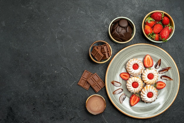 Vue de dessus appétissants biscuits sucrés avec sauce aux fraises et au chocolat à côté de bols de chocolat aux fraises et sauce sur table sombre