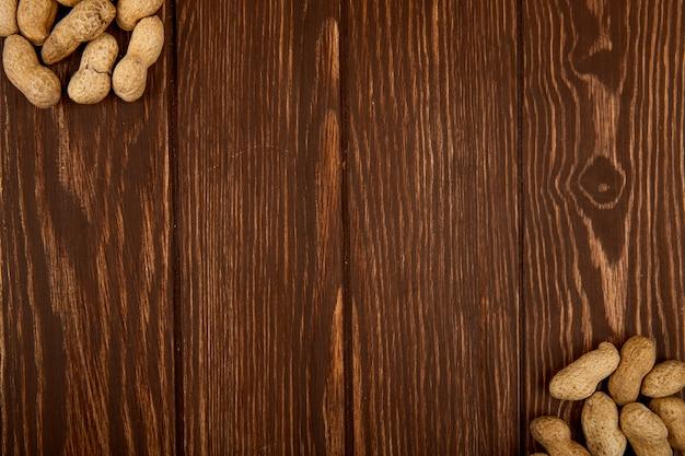 Vue de dessus des arachides en coque dispersées sur fond de bois avec espace copie