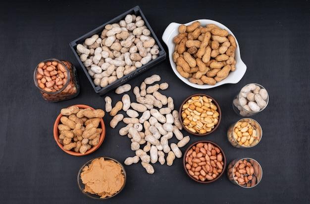 Vue de dessus des arachides crues, fraîches et frites et du beurre d'arachide dans une boîte, un pot et un bol, sur dark