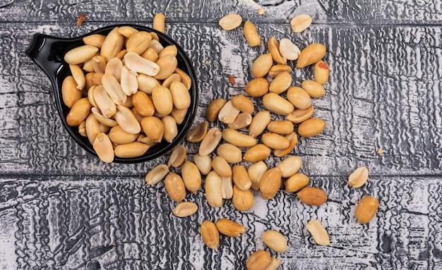 Vue de dessus des arachides en gros plan dans un bol sur l'horizontale en bois gris