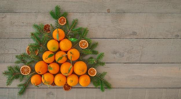 Vue de dessus d'un arbre de noël à base d'oranges fraîches et de copeaux d'orange séchée, branches d'un arbre de noël sur un mur en bois foncé avec espace de copie. idée alternative d'arbre de noël