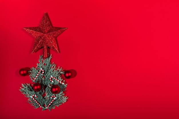 Vue de dessus d'un arbre de noël fait à la main avec une étoile, des boules et des jouets de bonbons sur fond rouge. notion de nouvel an