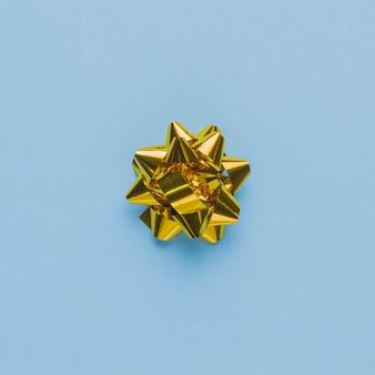 Vue de dessus d'un arc de cadeau unique sur une surface bleue unie