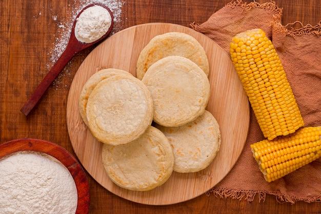 Vue de dessus des arepas avec du maïs et de la farine