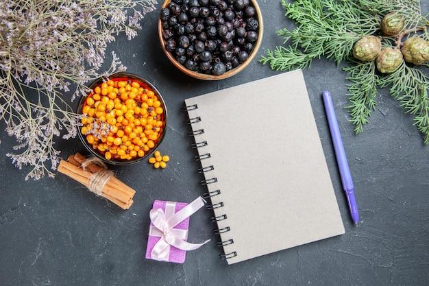 Vue de dessus l'argousier de cassis dans des bols petit cadeau bloc-notes stylo bâtons de cannelle sur une surface sombre