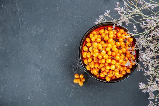 Vue de dessus de l'argousier dans un bol branche de fleurs séchées sur place libre de table rouge foncé