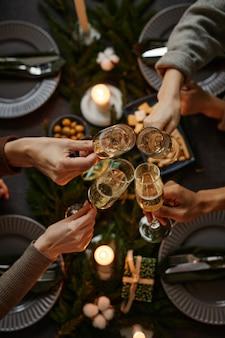 Vue de dessus arrière-plan de quatre personnes appréciant le dîner de noël ensemble et grillant avec du champagne gl...