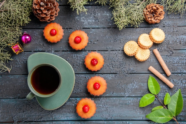 Vue de dessus arrondi cupcakes cerise branches de sapin jouets de noël cônes différents biscuits et une tasse de thé sur une table en bois foncé