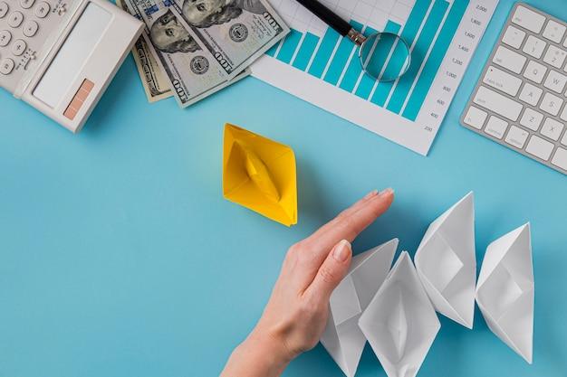 Vue de dessus des articles commerciaux avec courbe de croissance et main tenant des bateaux en papier