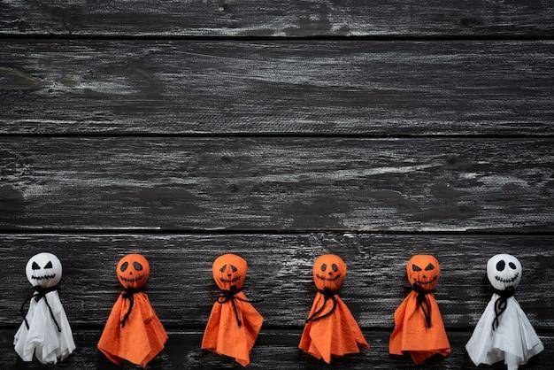 Vue de dessus de l'artisanat d'halloween, fantôme de papier blanc et orange sur backg en bois noir et blanc