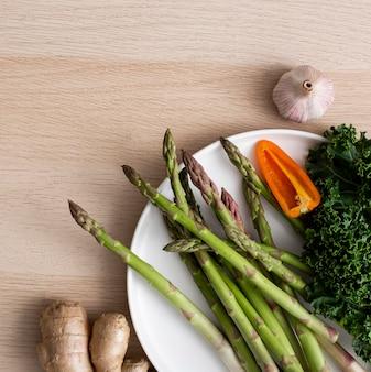 Vue de dessus asperges, poivre et chou frisé sur plaque avec gingembre et ail