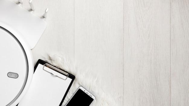 Vue de dessus de l'aspirateur avec smartphone et presse-papiers