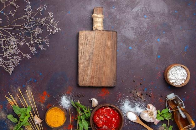 Vue de dessus des assaisonnements et de la sauce sur la couleur des aliments chauds épicés repas fond sombre
