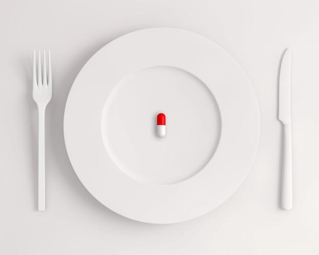 Vue de dessus d'une assiette blanche avec une fourchette à pilules et un couteau sur une surface blanche