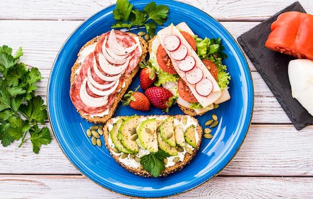Vue de dessus d'une assiette bleue avec trois types de sandwichs diététiques - alimentation saine et de bon goût - pain de blé entier avec graines