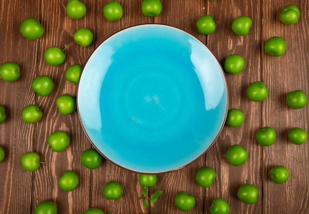 Vue de dessus d'une assiette bleue vide et de prunes vertes aigres disposées autour d'une table en bois