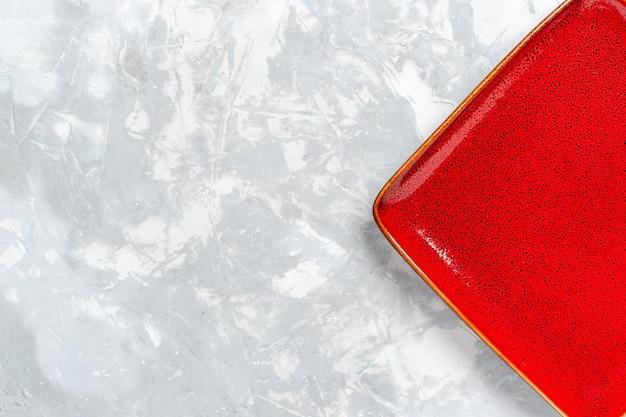 Vue de dessus assiette carrée vide ed rouge sur un bureau blanc
